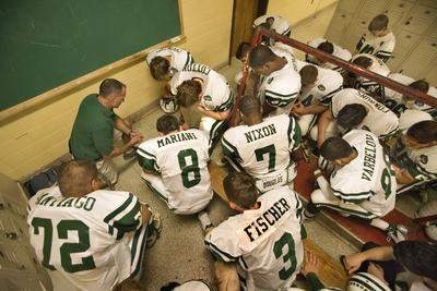 Coach Marcus Borden of East Brunswick High School takes a knee as a player says a pregame prayer in the locker room moments before a game between East Brunswick and Woodbridge High School in 2007. (Boston Globe/Stan Grossfeld)